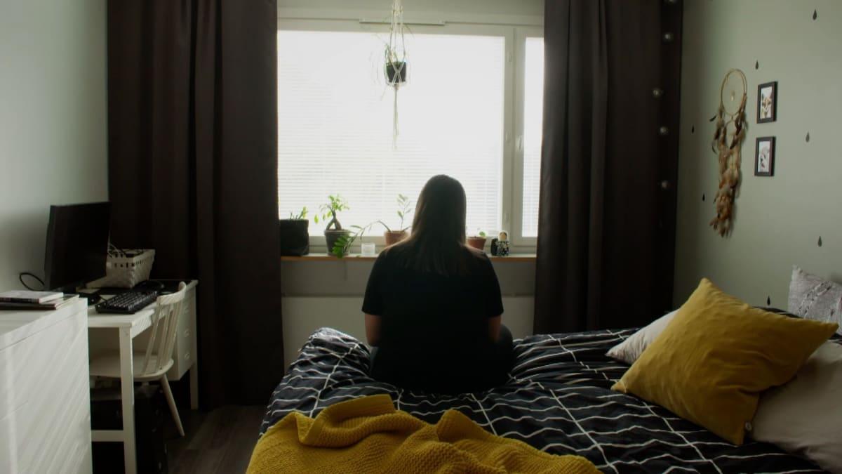 Nainen istuu sängyn reunalla ja katsoo ikkunasta ulos.