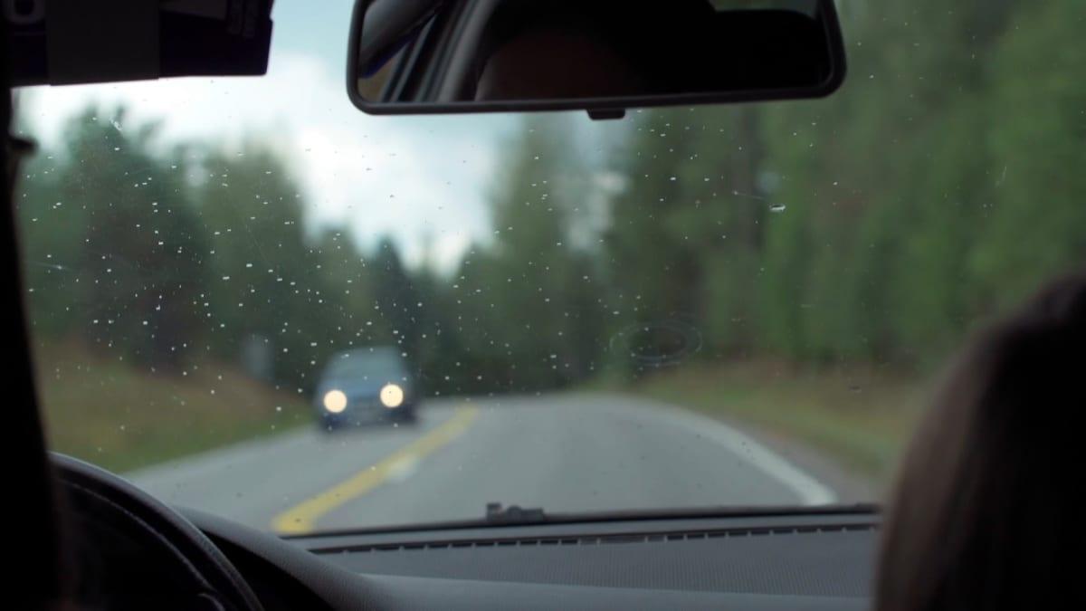 Auton tuulilasi, jossa vesipisaroita. Tie näkyy edessä.