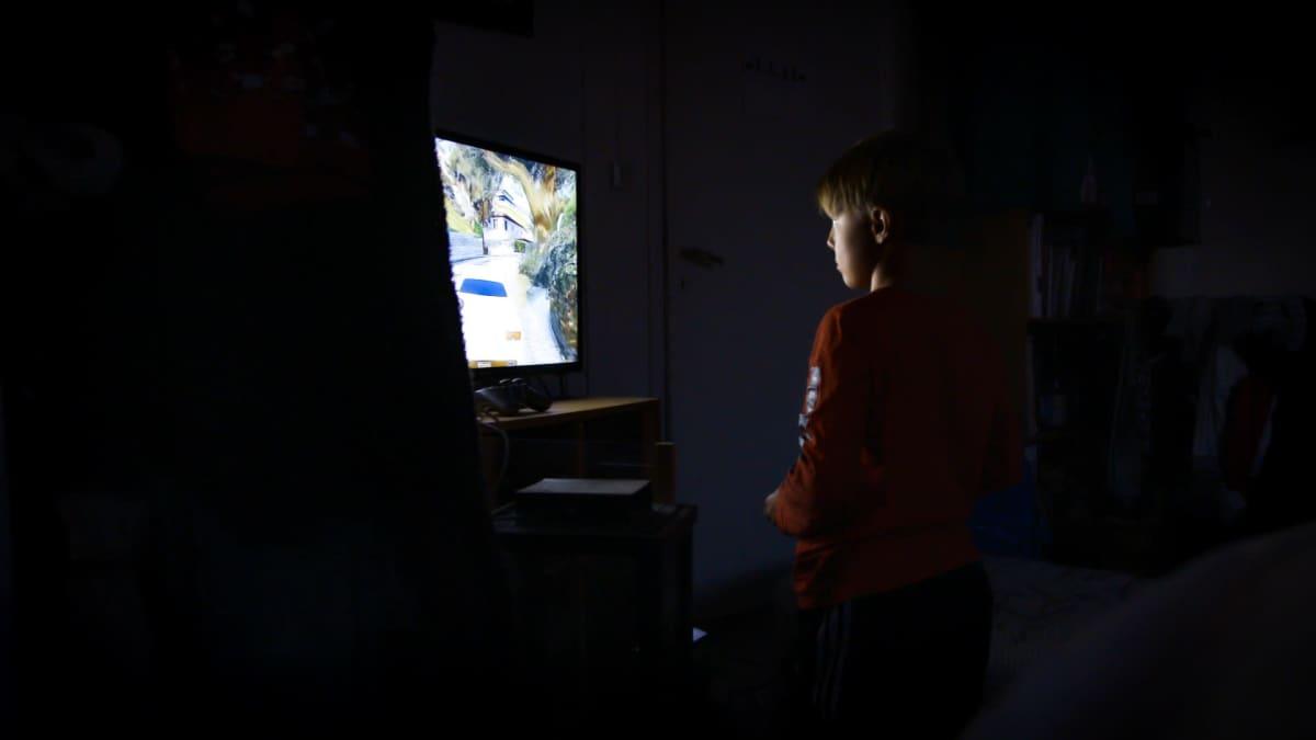 Viljami-poika on polvillaan television ääressä ja pelaa autopeliä