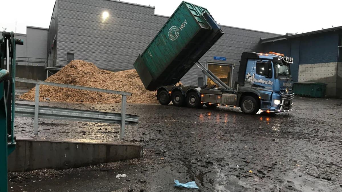 Kuorma-auton lavalta kaadetaan haketta kompostointilaitoksen edessä