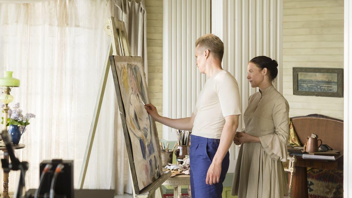 Johannes Holopainen ja Laura Birn seisovat maalaustelineen edessä.