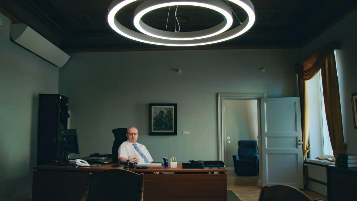 Työministeri Jari Lindströmin viimeinen työpäivä, hetki ennen seremonioita. Lindström istuu työpöytänsä takana.