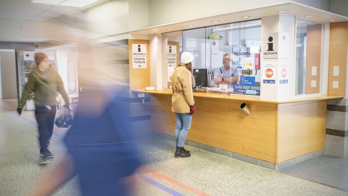 Ihmisiä aulassa sairaalan vahtimestarin tiskin luona.