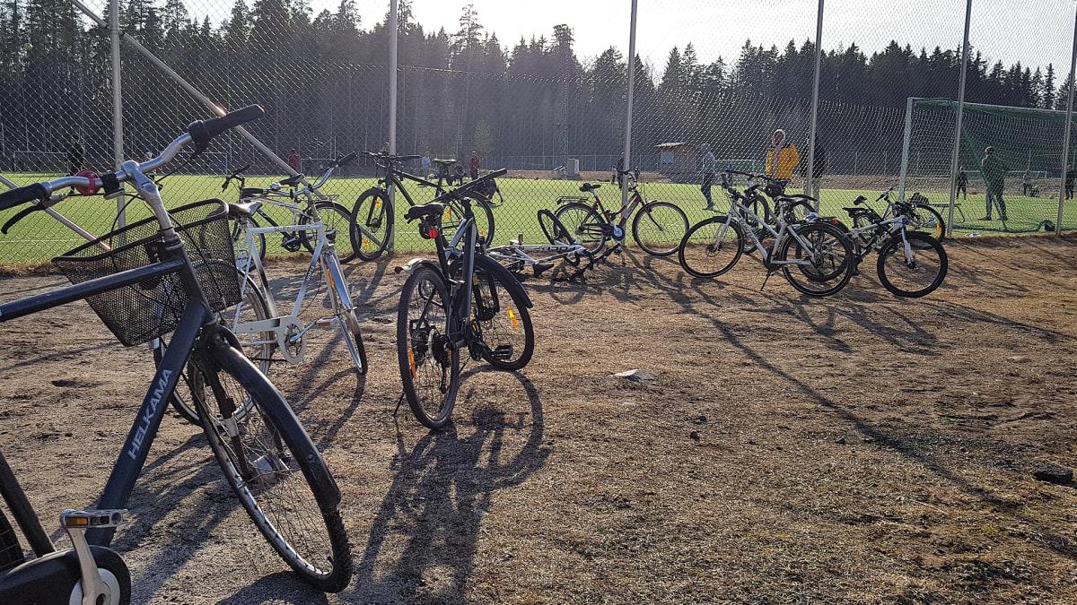 Polkupyöriä palloilukentän laidalla