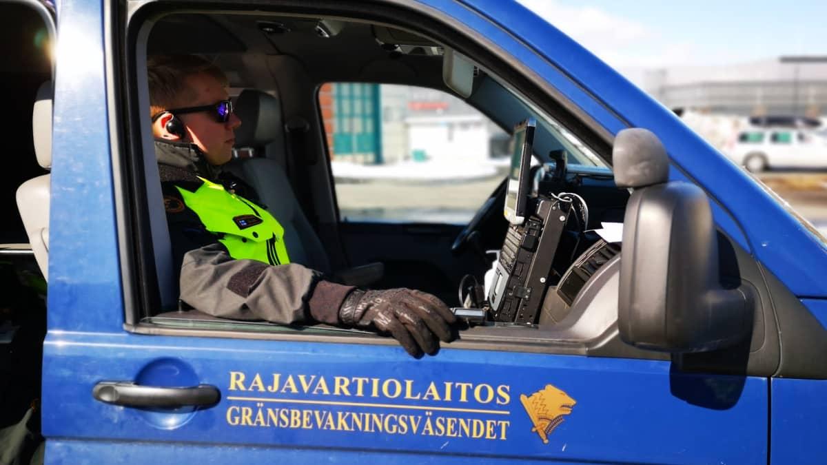 Rajavartija istuu autossa suorittamassa rajaliikenteen valvontaa.