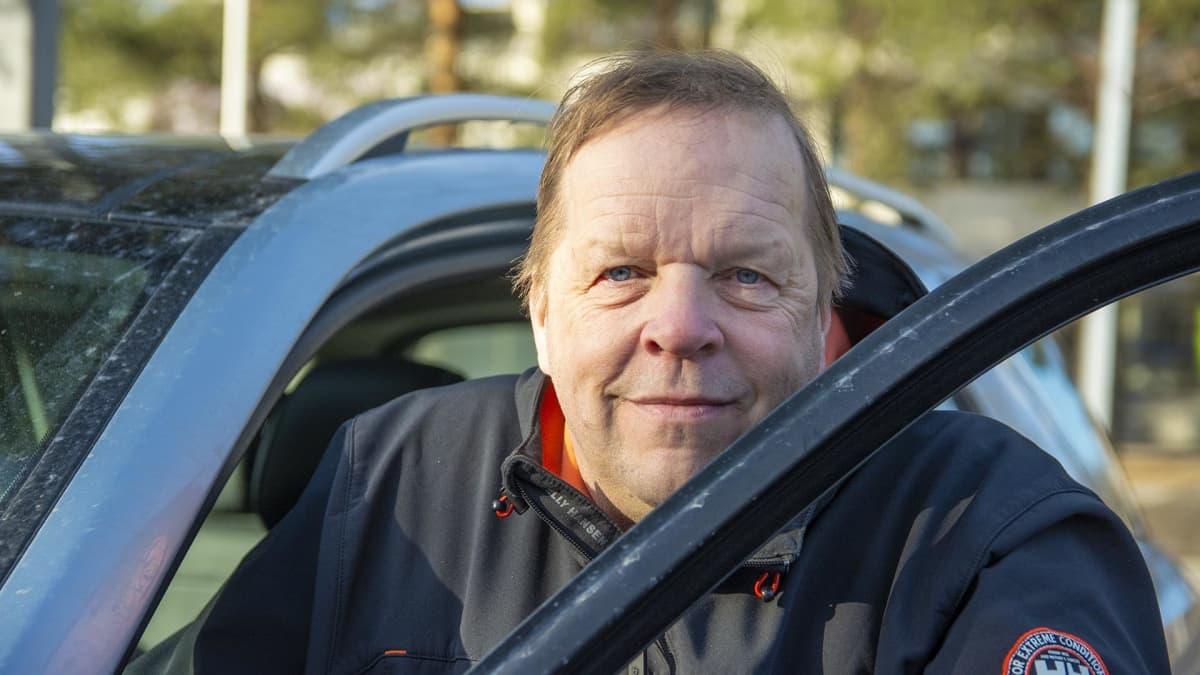 Antti Kela nojaa auton oveen.