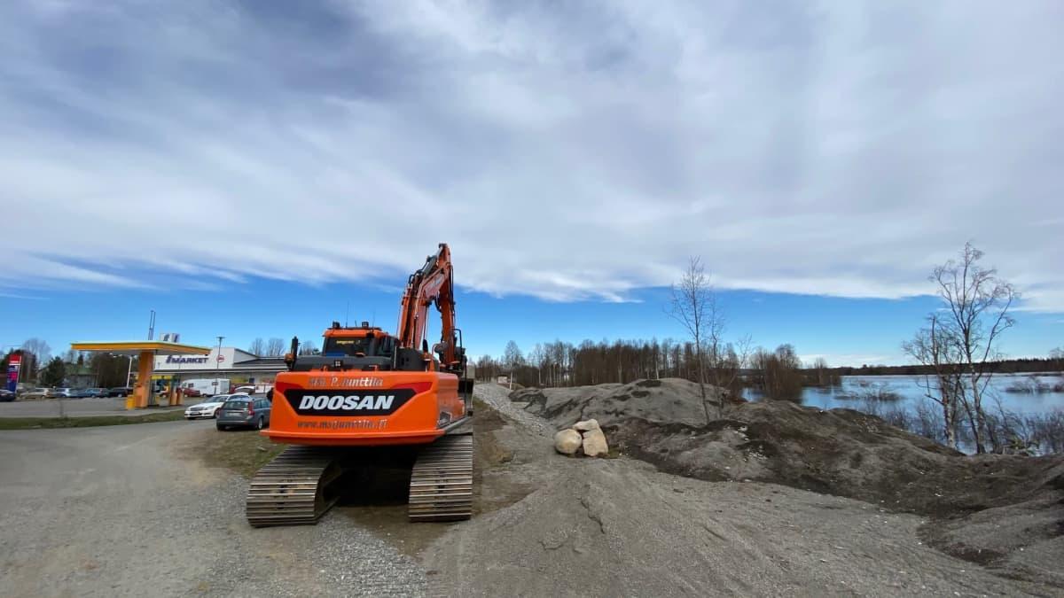Maansiirtokone valmiudessa Kittilässä tulvivan Ounasjoen rannalla penkereen päässä.