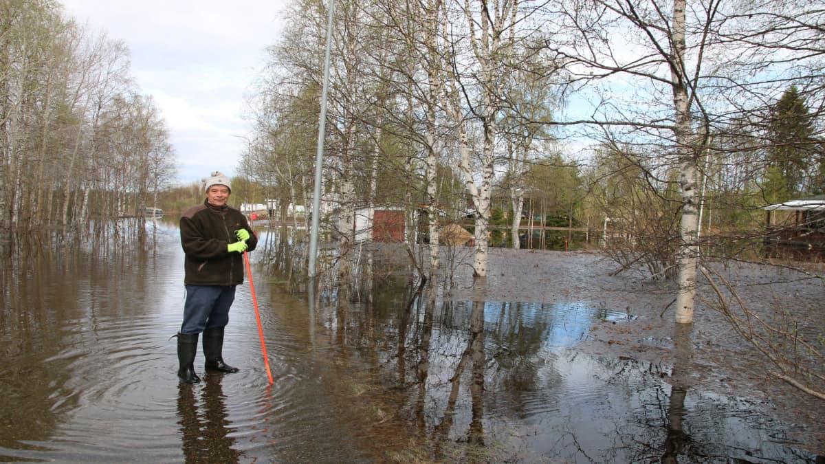 Markku Lemmetty tulvaveden ympäröimän mökkinsä lähellä