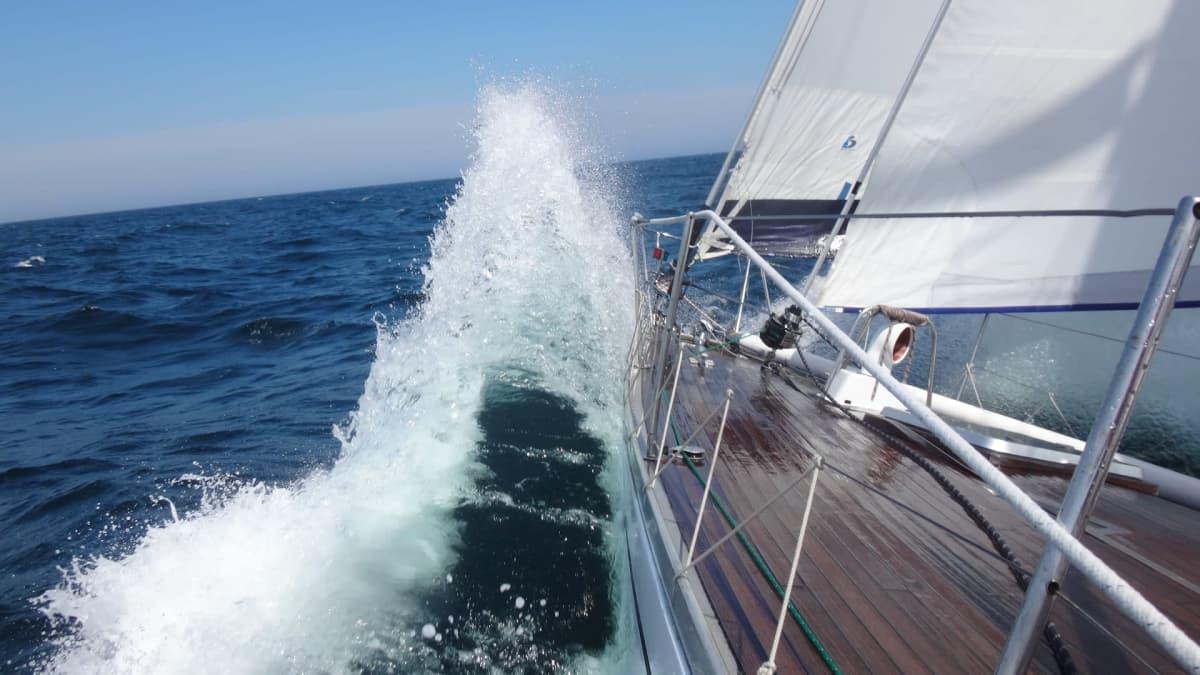 Aallot pärskähtää purjeveneen kylkeen.