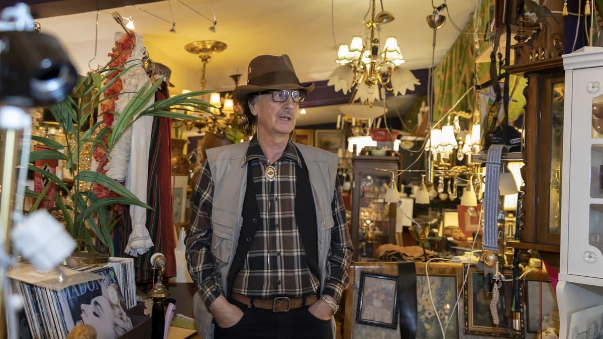 Mies seisoo  keskellä antiikkikauppaa.