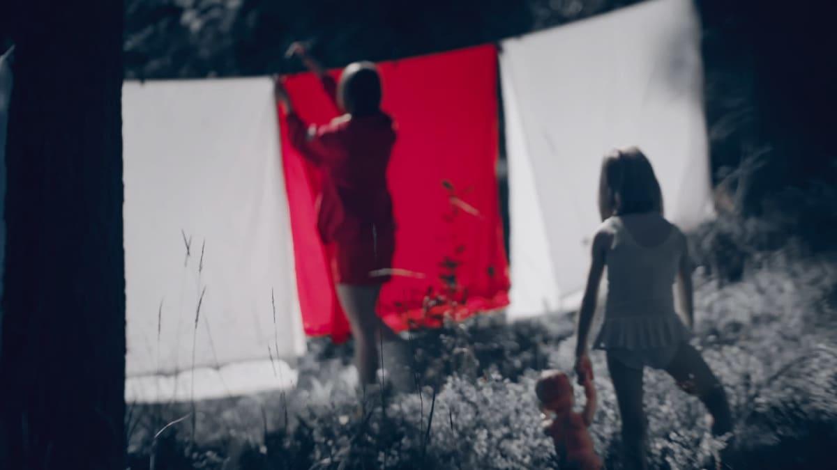 Pikkutyttö katselee kun nainen ripustaa lakanoita pyykkinarulle