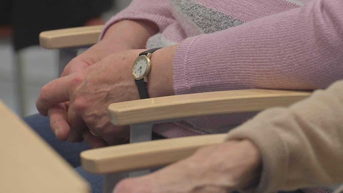 En person med rosa tröja och armbandsur sitter med knäppta händer vid ett bord.