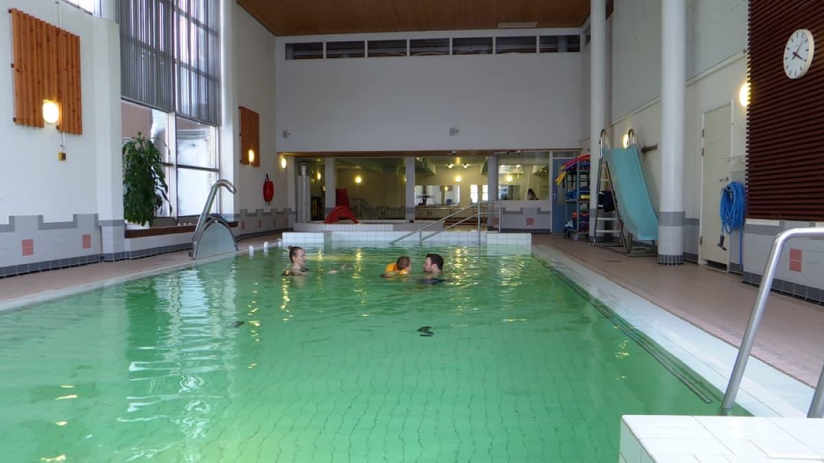 Perhe uimassa uimahallissa, ainoat altaassa, ei muita.