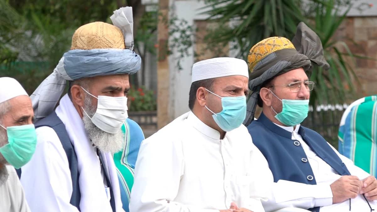 Pakistanilaisia heimonvanhimpia perinteisissä tunikamaisissa asuissa, maskit kasvoillaan.