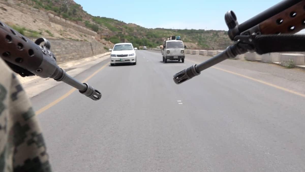 Kahden aseen piiput osoittavat vuoristotiellä vastaan tulevaa liikennettä kohti.