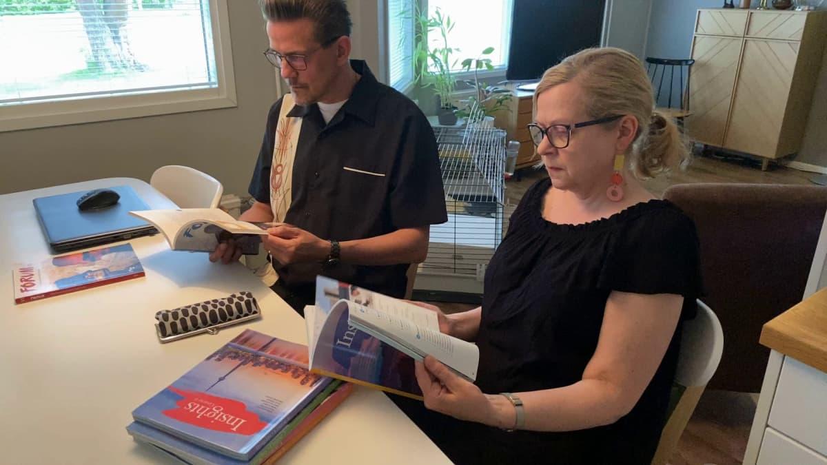 Maarit Kuusiluoto-Männikkö ja Tapani Männikkö selaavat oppikirjoja keittiön pöydän ääressä