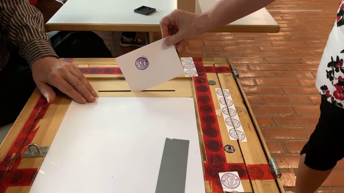Nainen pudottaa äänestyslipuketta vaaliuurnaan