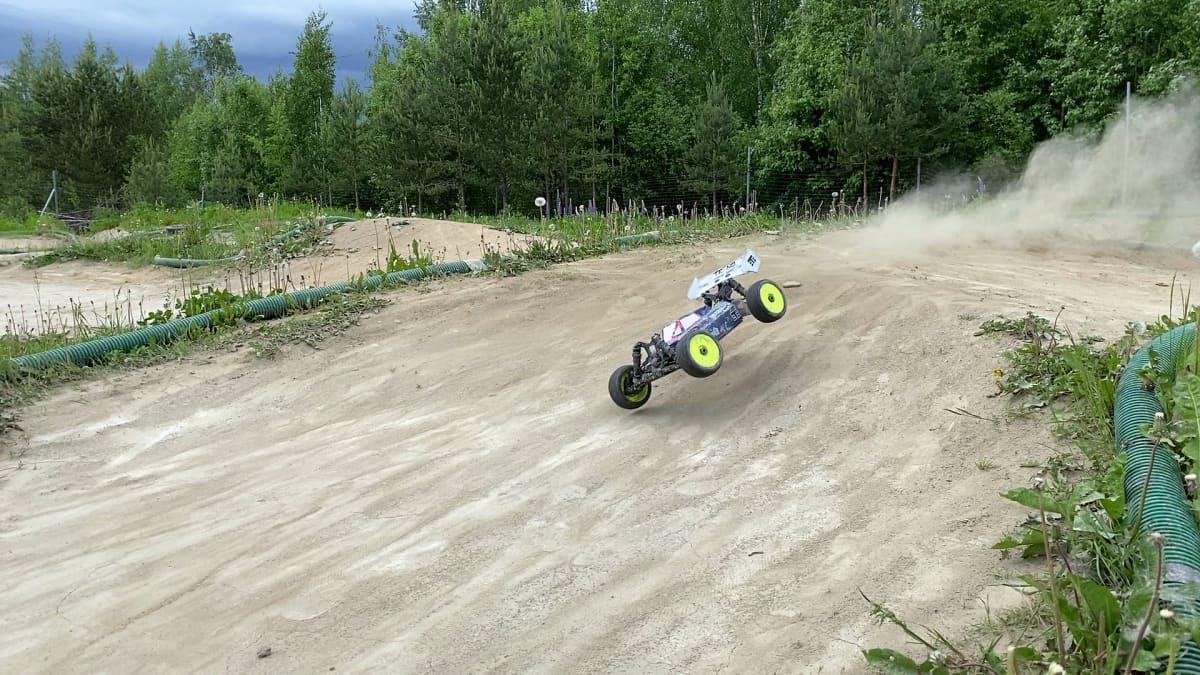 Rc-auto kiitää maastoradalla ja renkaista lentää pölyä