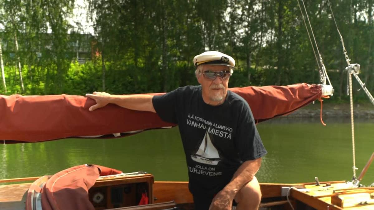 Kipparinlakkiin ja peililaseihin sonnustautunut mies mahonginvärisen veneen kannella.