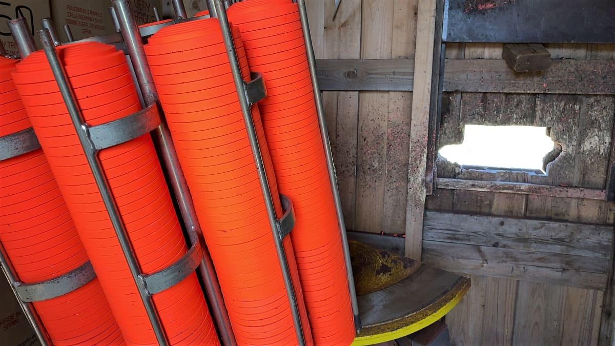 Oranssinvärisiä savikiekkoja taivaalle ampuva kone kuvattuna puuvajan sisäpuolelta