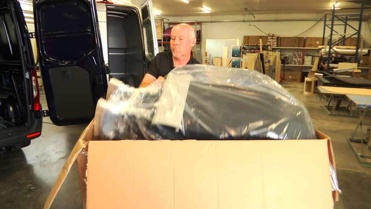 mies halissa nostaa tavaraa laatiokosta
