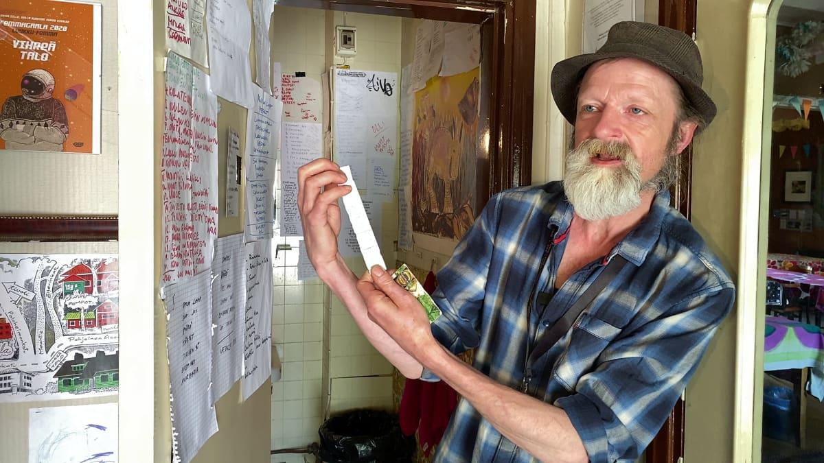 Vihreän talon isäntä Olli Soini vessan ovella kädessään biisilista