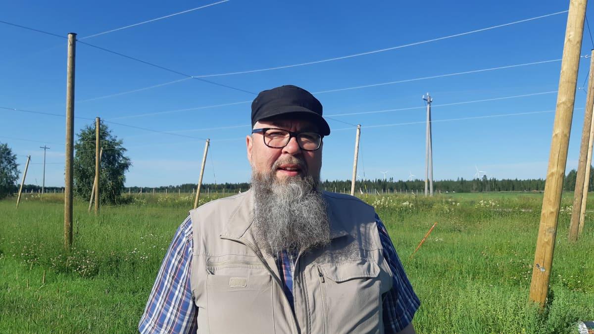 Louen maatalousoppilaitoksen toimipaikkapäällikkö Jarmo Saariniemi seisoo koeviljelmäalueella, taustalla näkyy humalaköynnöksiä varten pystytettyj pylväitä