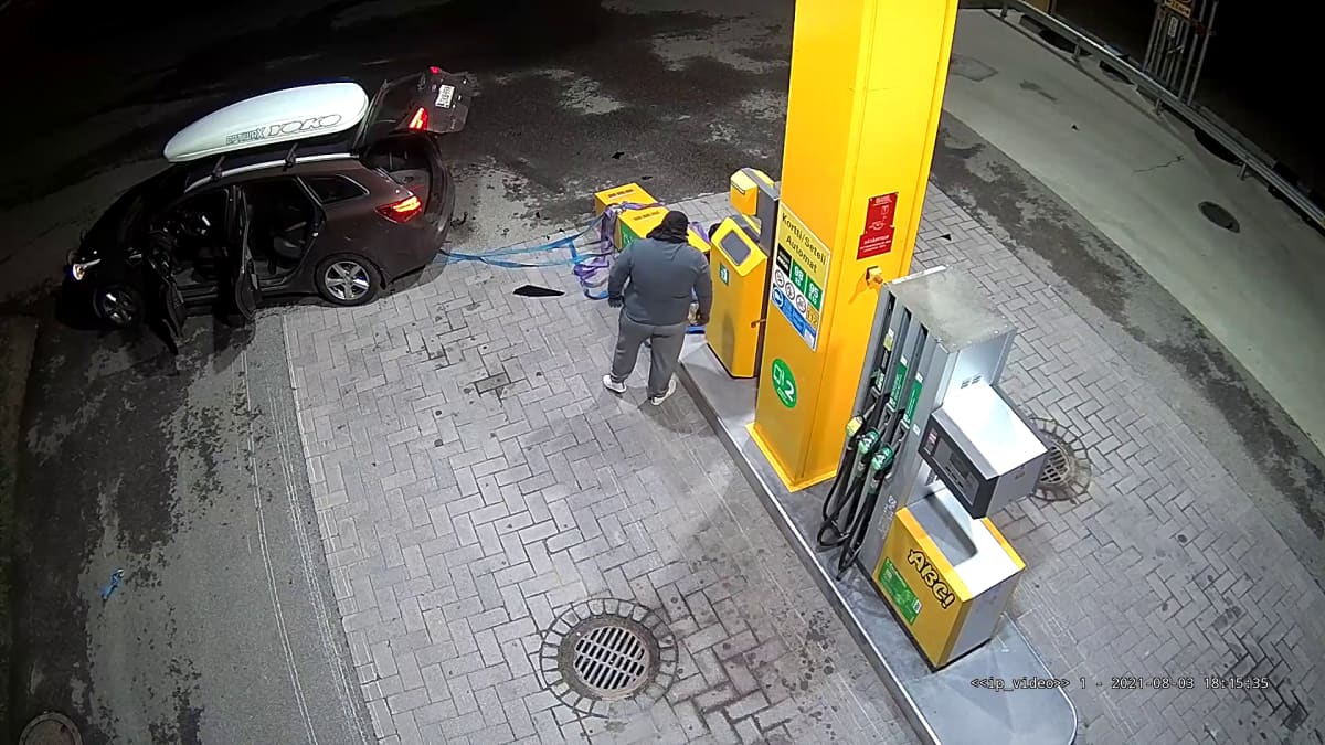 Valvontakamerakuva ylhäältäpäin,auto on kiinnitetty liinalla kiinni kaatuneeseen bensa-aseman maksuautomaattiin. Yksi mies seisoo selin kameraan asemalla.