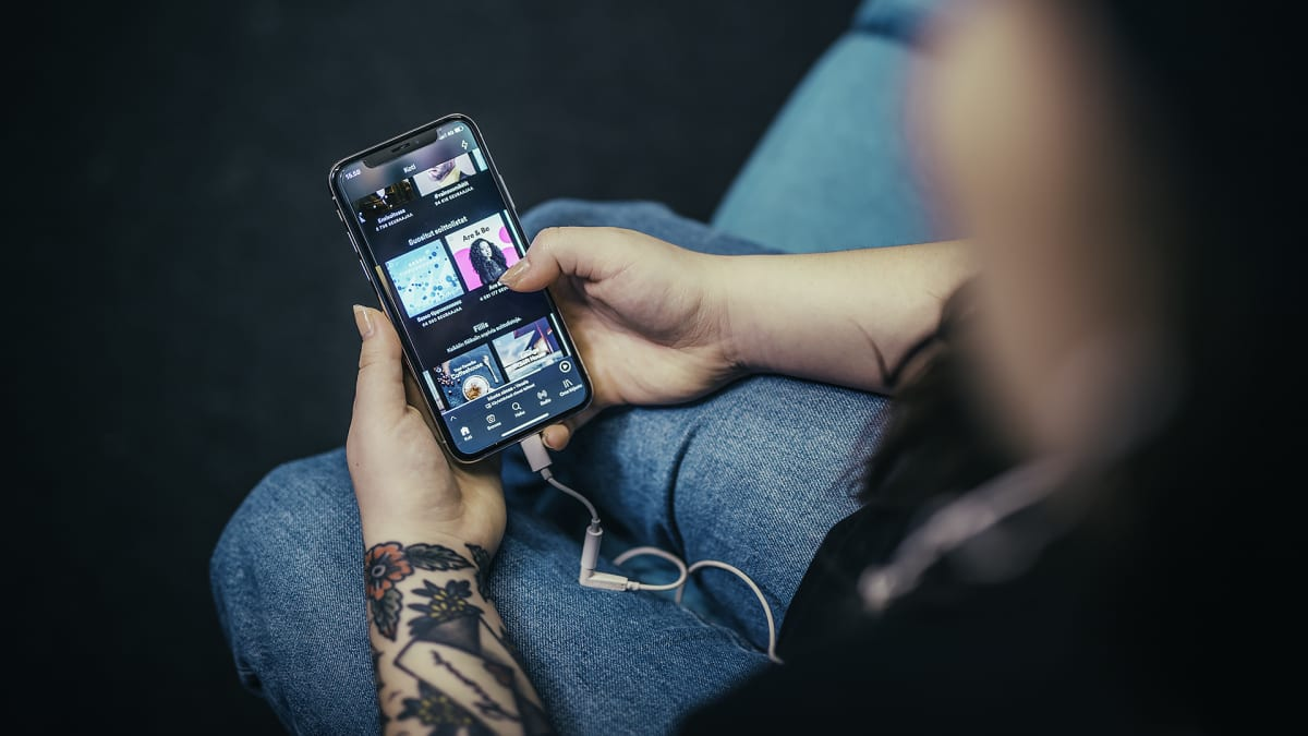 Puhelin kädessä sohvalla, Spotify auki.