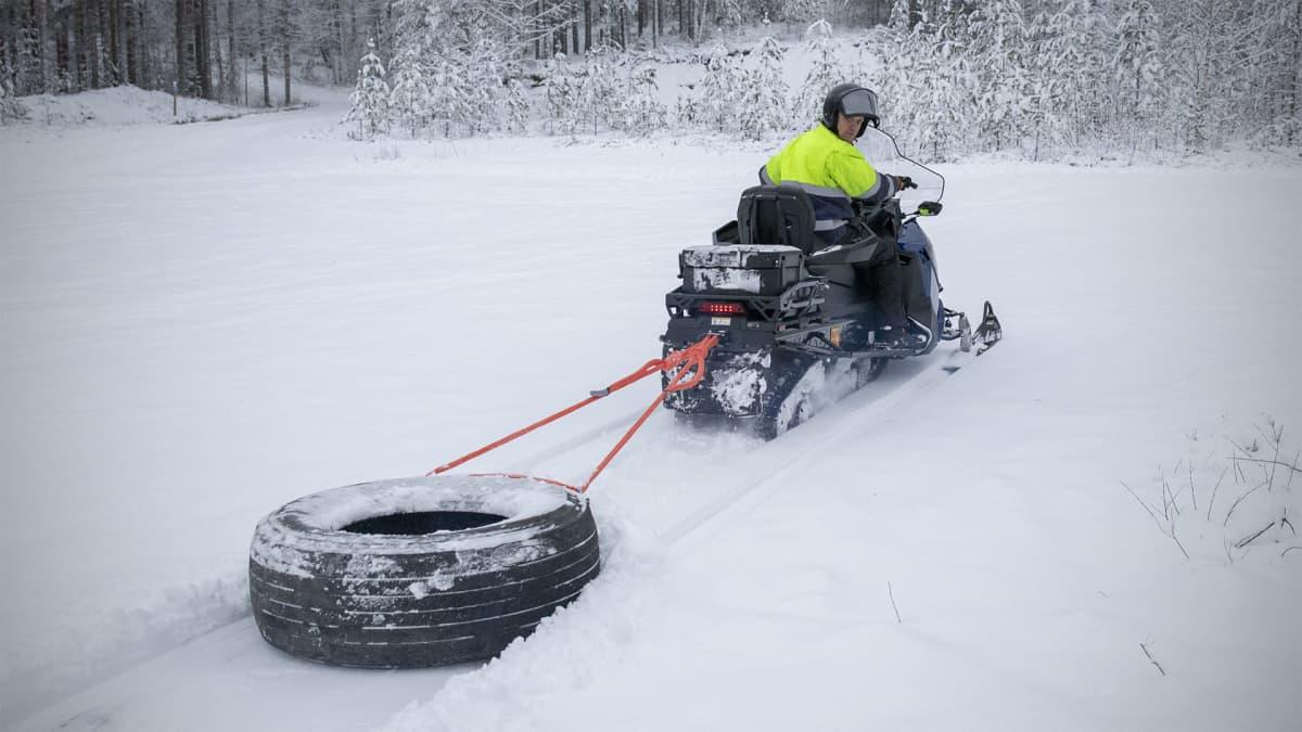 Harry Jussila vetään moottorikelkalla rengasta, joka avaa kävelijöille uraa lumeen.