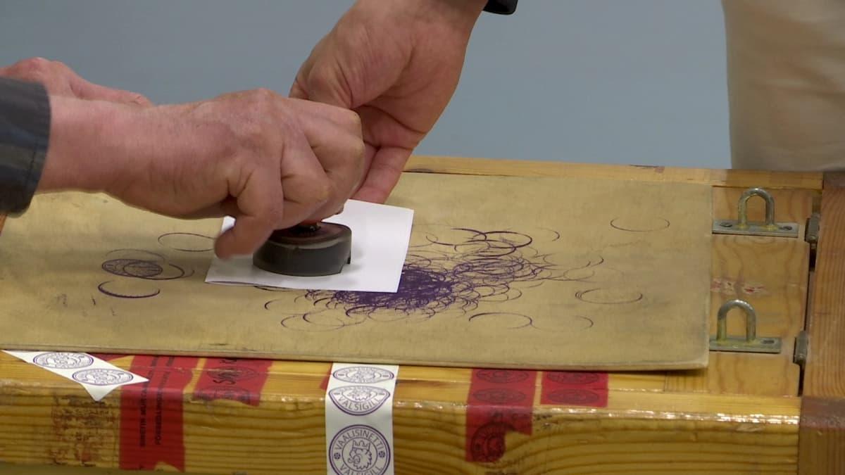 Äänestyslipuketta leimataan.