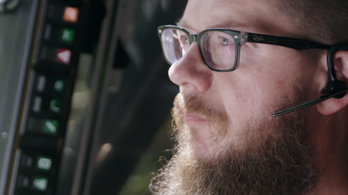 Metsäkoneyrittäjä Tero Kurula lähikuvassa monitoimikoneen ohjaamossa