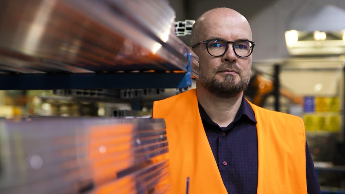 Steran tuotantopäällikkö Tero Marjamäki katsoo kameraan metallilevy pinon vieressä.
