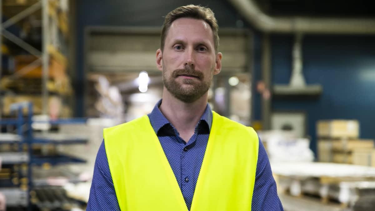 Forssan työllisyyspalvelujen Jukka Lindmansinisessä kauluspaidassa ja keltaisessa huomiliivissä katsoo vakavasti kameraan konepajayritys Steran tuotantoiloissa.