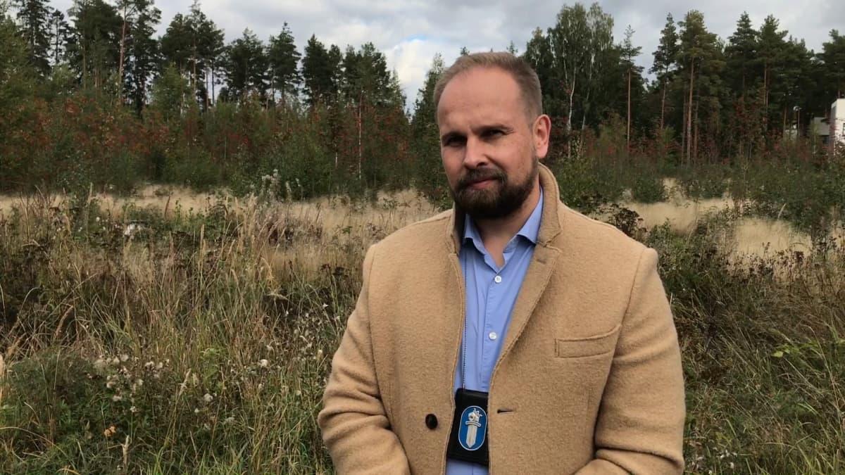 Rikoskomisario Jarmo Katila seisoo syksyisen niityn laidalla kaulassaan poliisin virkamerkki