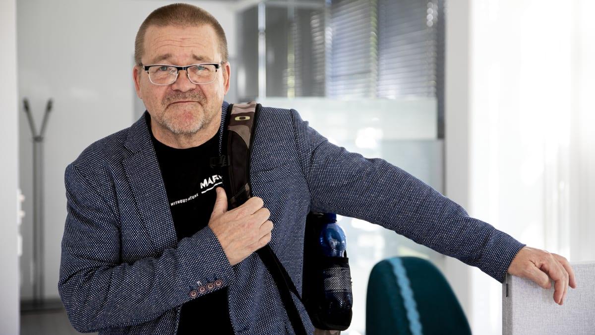 Jukka Linberg nojaa hymyillen toimiston sermiin.