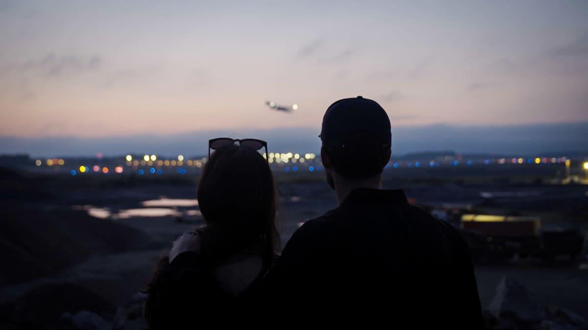 Pariskunta katselee maisemaa selät kameraan päin. Taustalla näkyy häilyen lentokenttä ja ilmaan nouseva lentokone.