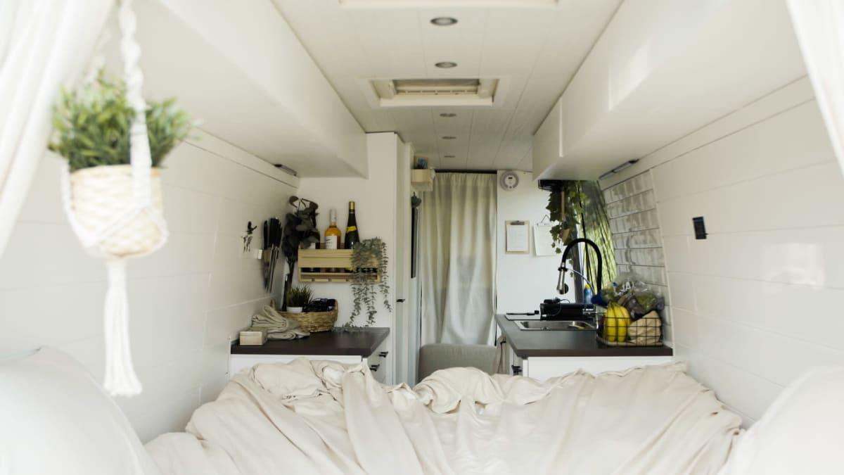 Pakettiauton takaosa, joka on sisustettu valkoisen sävyiseksi. Takana näkyy pieni keittiö, edessä sänky.