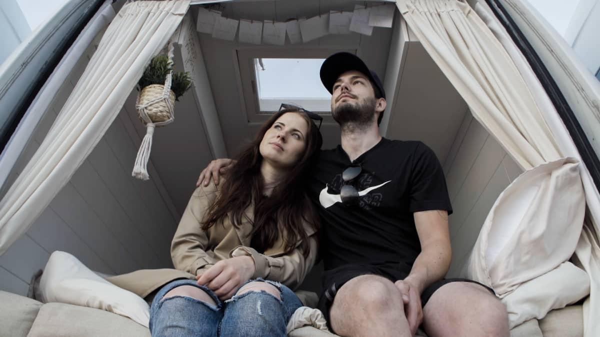 Pariskunta istuu pakettiauton perässä vierekkäin, nainen miehen kainalossa.