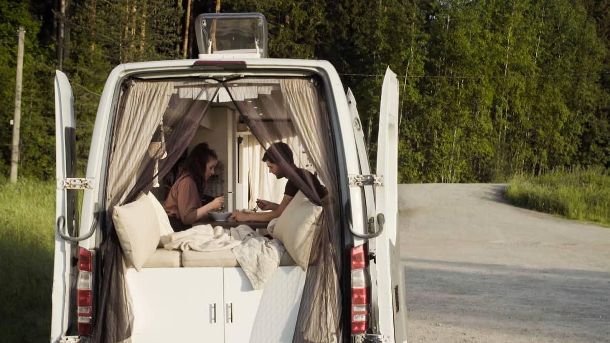 Pakettiauto on pysäköity tien laitaan maaseudulla. Takaovet ovat auki, ja sisällä näkyy pariskunta syömässä pöydän ääressä.