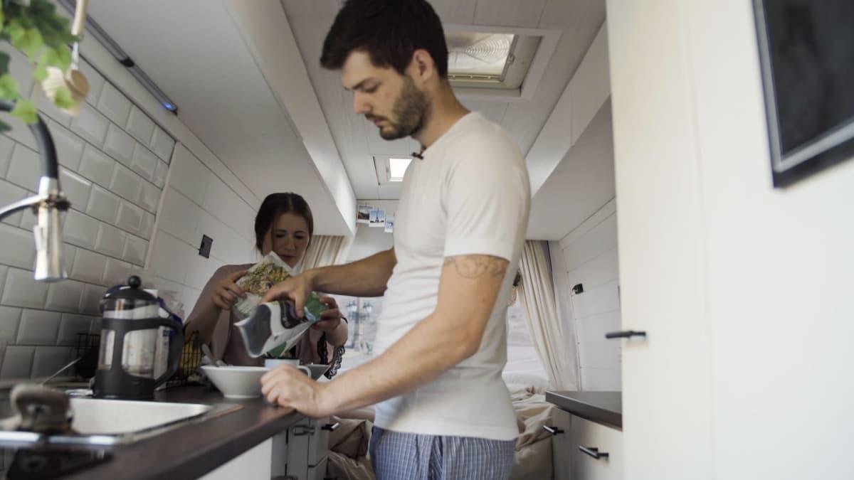 Pariskunta pakettiautokodin keittiössä tekemässä aamiaista.