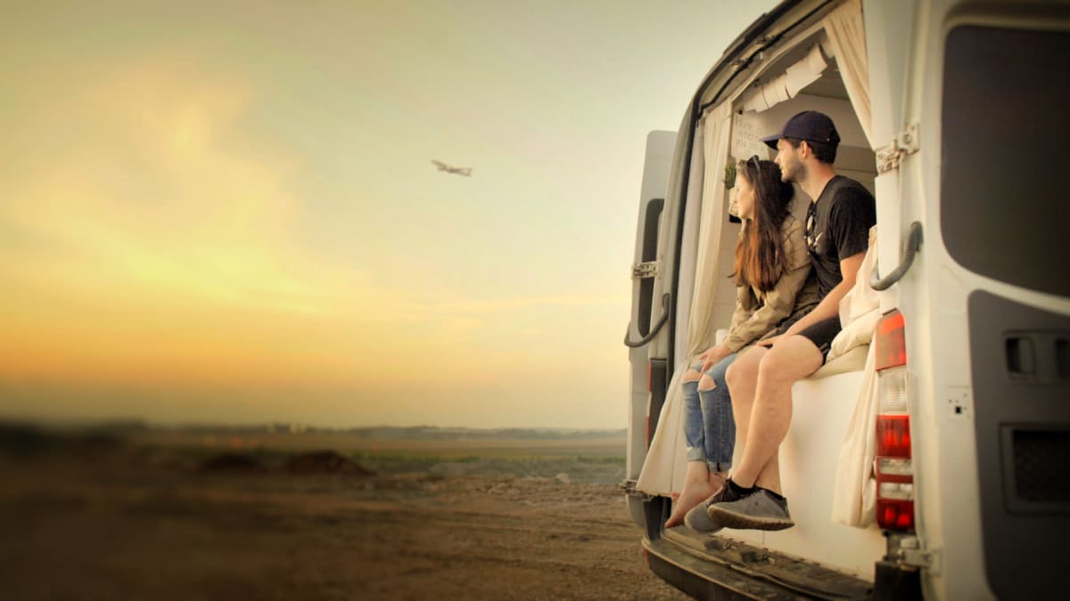 Pariskunta istuu pakettiauton perässä jalat ulkona roikkuen. He katselevat auringon laskiessa taustalla näkyvän karun lentokentän lentokoneita, joista yksi on nousemassa ilmaan.