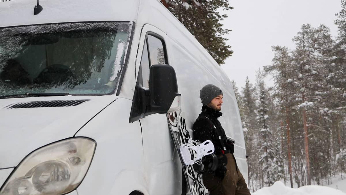 Mies nojailee pakettiauton kylkeen. On talvi. Pakettiautoa vasten nojaa myös lumilauta.