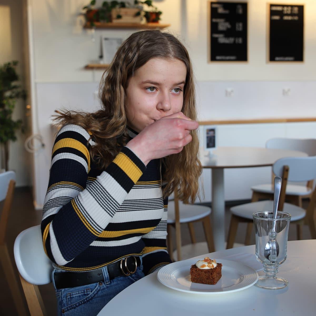 Salla Mäki syö leivosta kahvilassa.