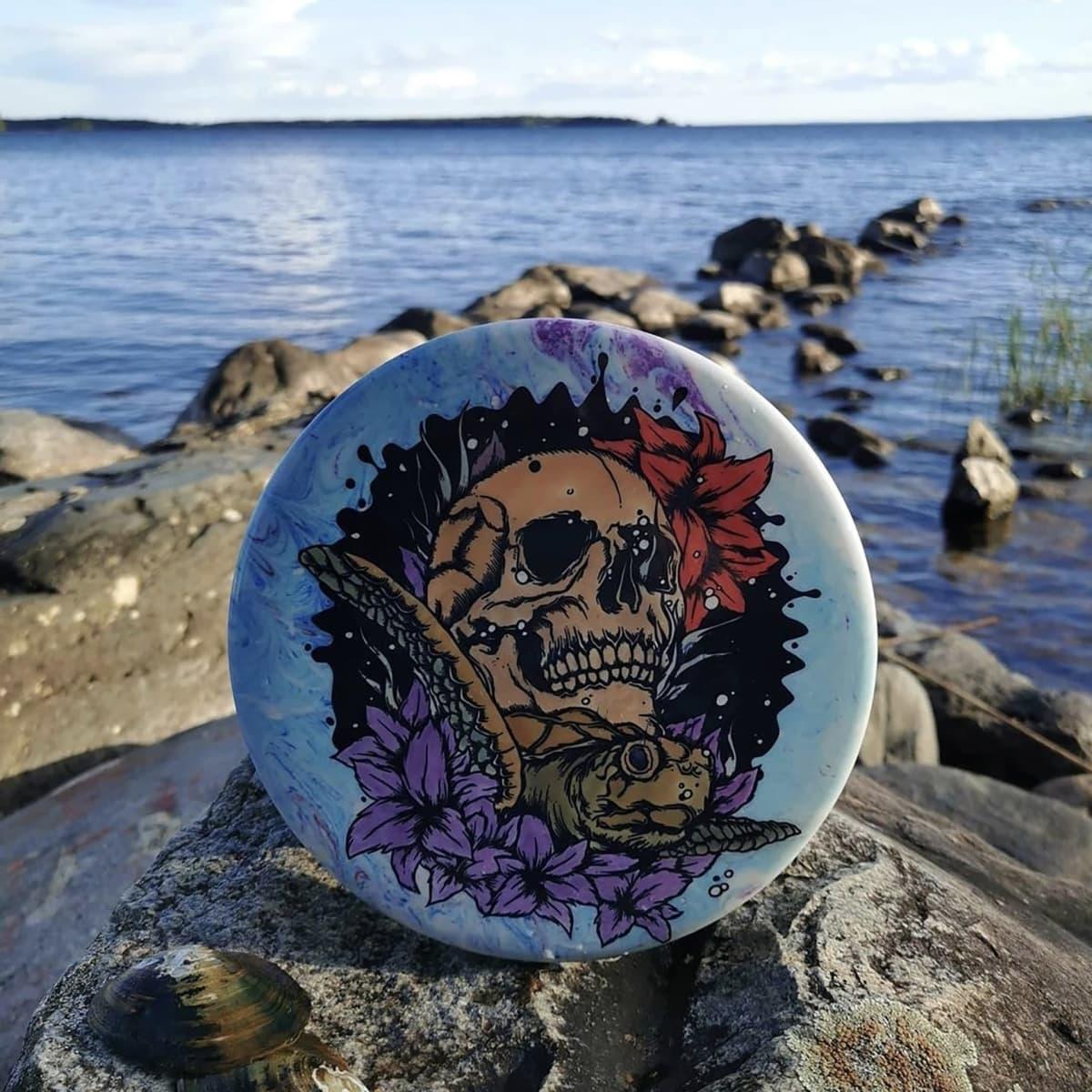 Pääkallokuviolla maalattu liitokiekko rantakivellä, taustalla merimaisemaa.