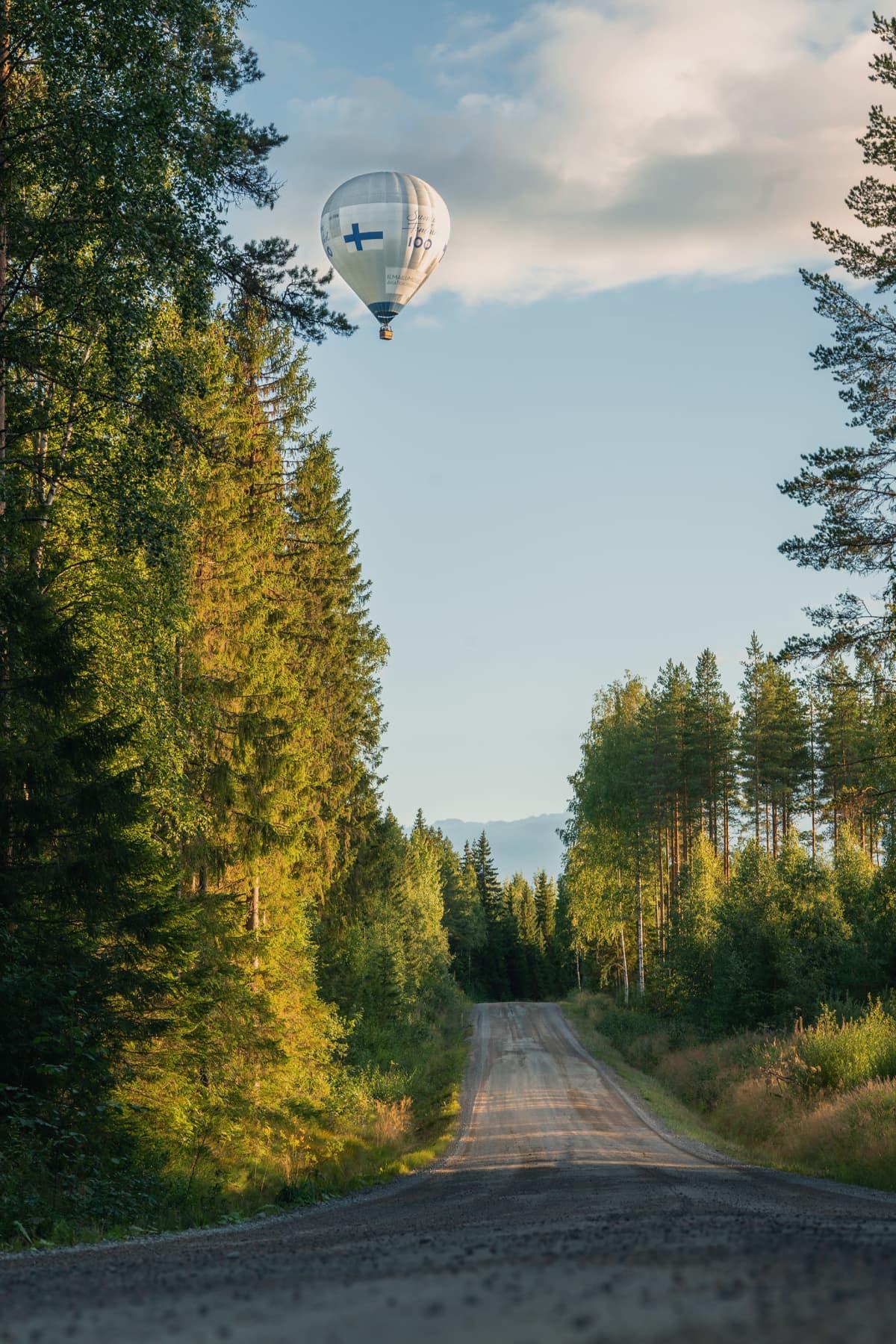 Kuumailmapallo lentää metsäautotien yllä.