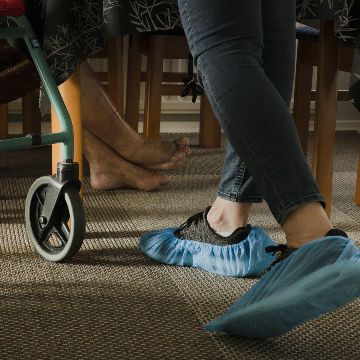 Vanhuksen ja kotihoitajan jalat pöydän alla.
