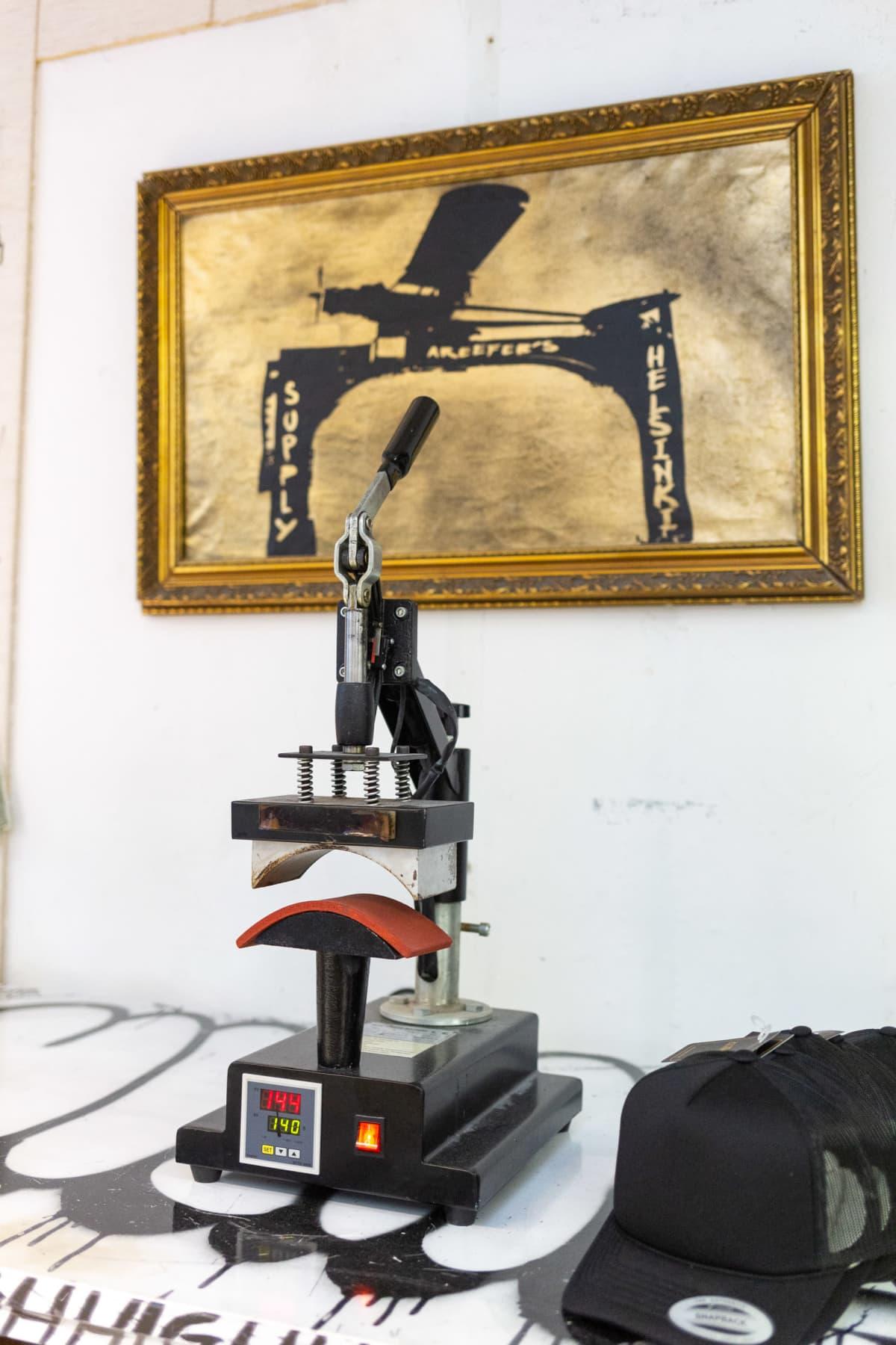 Lippisten printtaamiseen tarkoitettu prässi pöydällä.