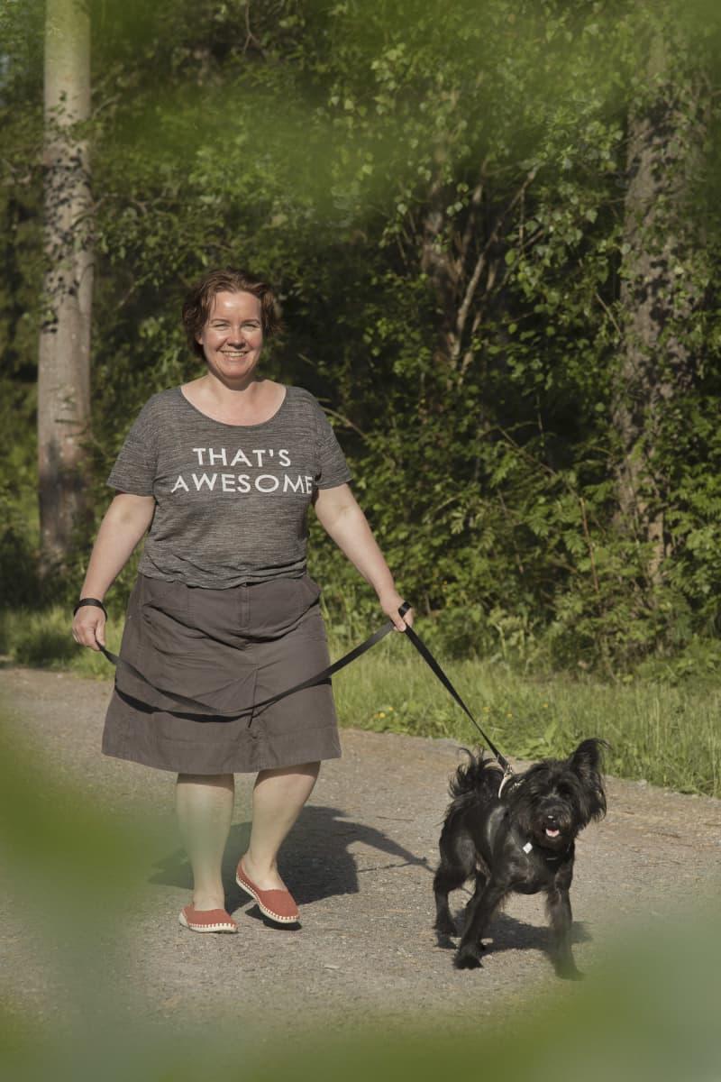 Mimmi Tick ulkoiluttaa mustaa koiraa hymyillen.
