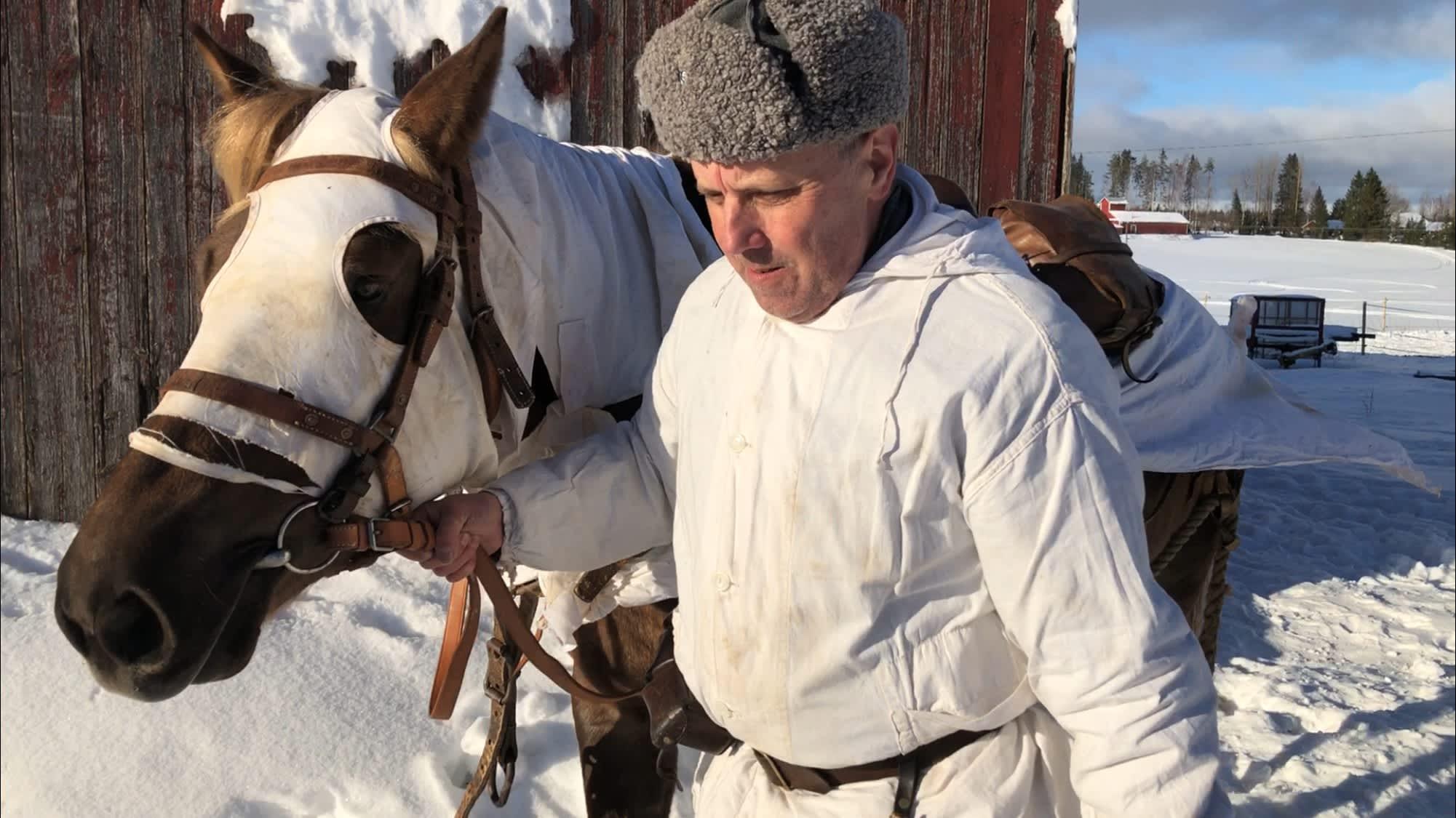 Lähikuva ratsuri Matti Peuralasta taluttamassa hevosta pihalla